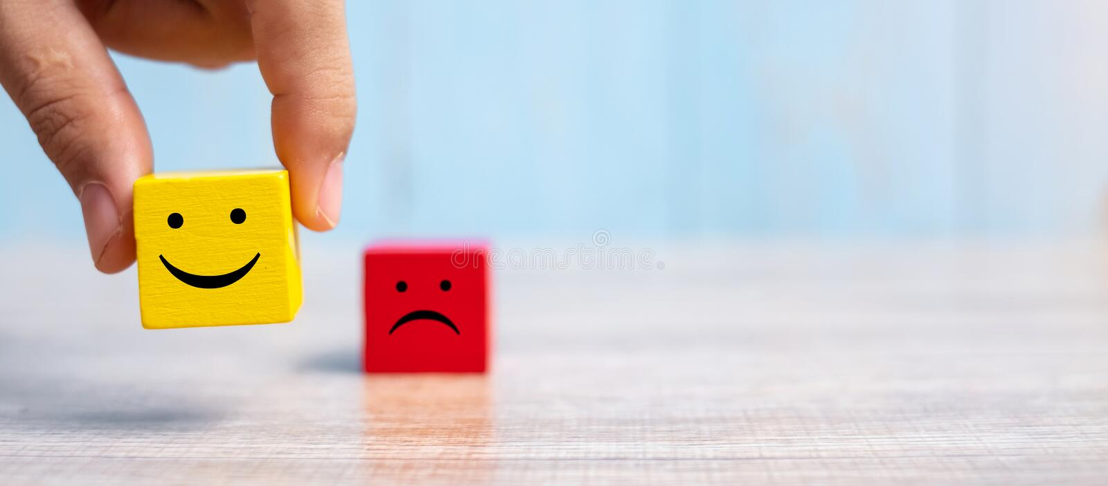 Smile face on yellow wood cube and sad face icon on red wood cube. Service rating, ranking, customer review, satisfaction and. Emotion concept stock photos