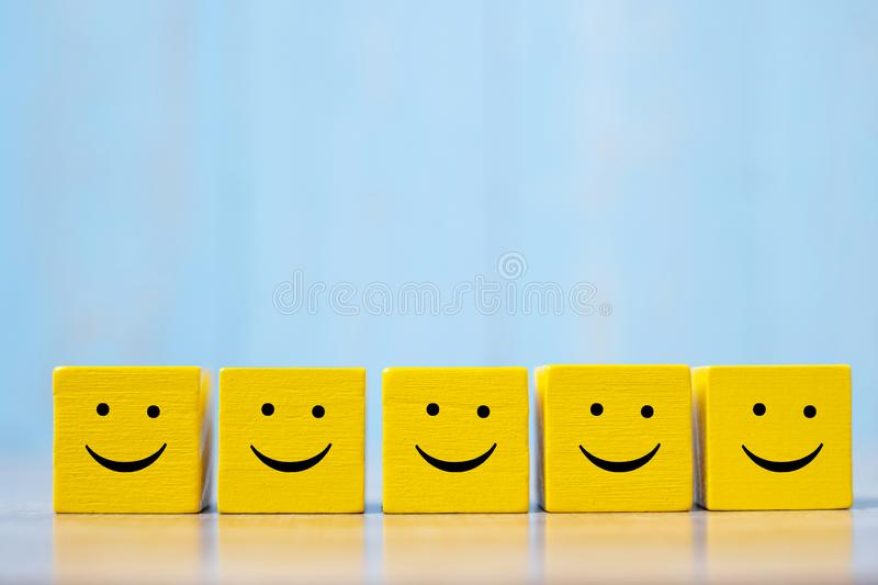 Smile face on yellow wood cube. Service rating, ranking, customer review, satisfaction and emotion concept.  royalty free stock photography