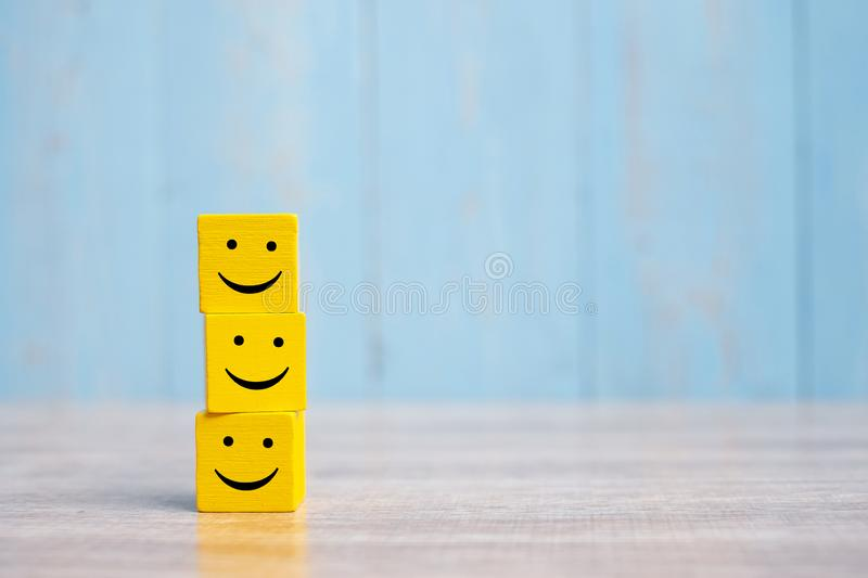 Smile face on yellow wood cube. Service rating, ranking, customer review, satisfaction and emotion concept.  stock image