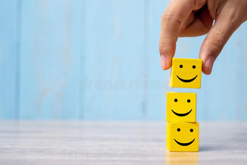 Smile face on yellow wood cube. Service rating, ranking, customer review, satisfaction and emotion concept.  royalty free stock images