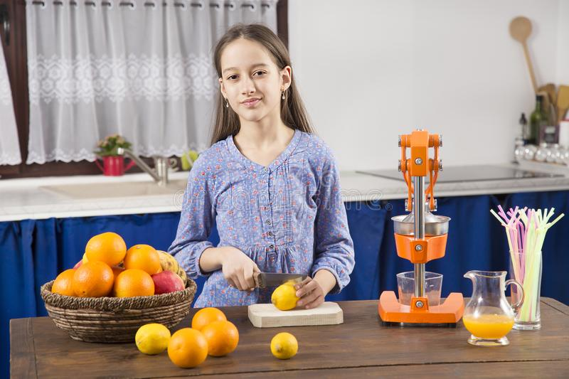 Smile girl in kitchen make a juice royalty free stock photography