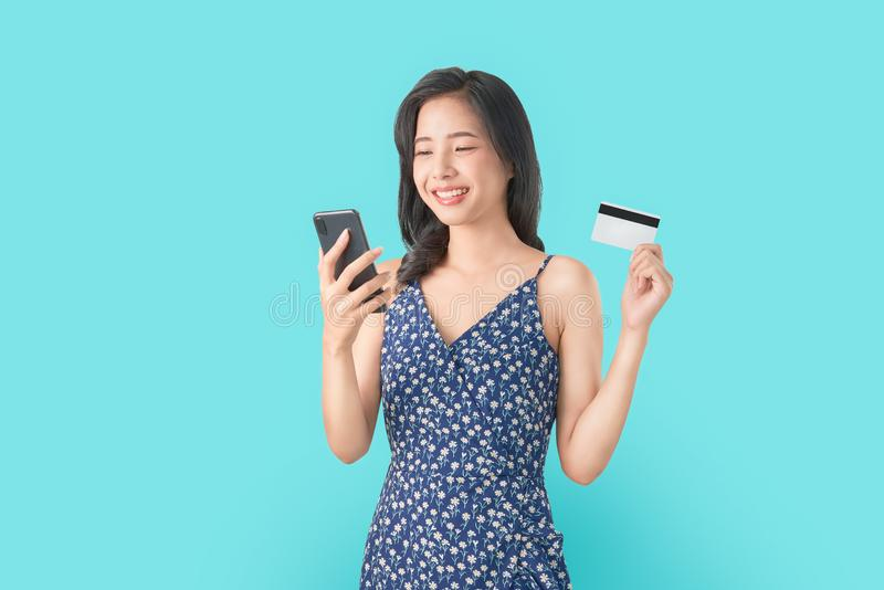 Smile happily Asian woman holding smartphone and credit card shopping online on blue background. Smile happily Asian woman holding smartphone and credit card stock photo