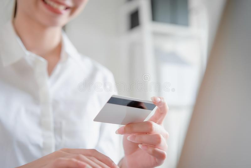 Smile happily Asian woman shopping online and holding credit card and enter the payment code for the product. Smile happily Asian woman shopping online and stock photos