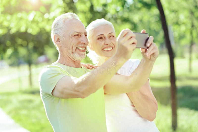 Progressive aged people taking a photo. Smile. Happy smiling progressive aged people taking a photo with a help of a smartphone stock photos