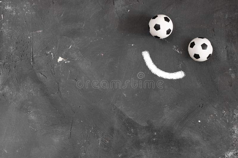 Smile made of Two small football balls and chalk line on dark textured blackboard background with copy space for text. And design. Top view. Creative concept royalty free stock photos
