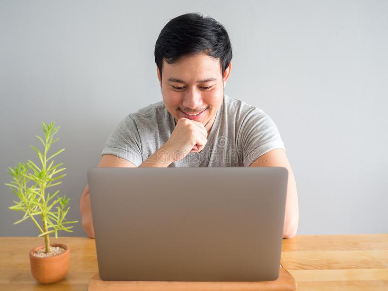 Smile man is feeling happy with his work in the laptop. royalty free stock images