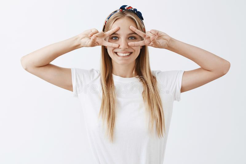 Smile never been so cute. of charming and happy carefree european girl with blond hair, showing victory or peace signs royalty free stock photos