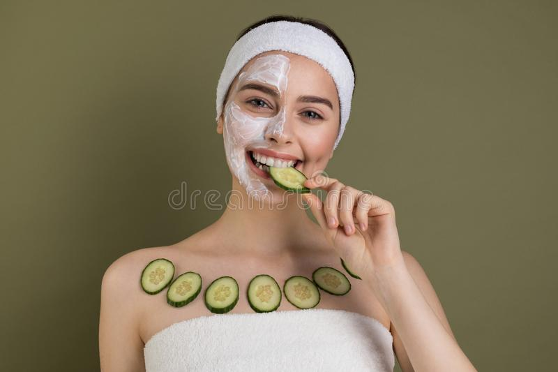 Smile positive caucasian girl with clay mask and organic cucumber slices. Spa woman caring for her skin and health, eating organic food  on green background stock photo