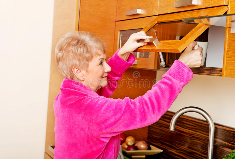 Smile senior woman taking mug from a kitchen cabinet royalty free stock photography