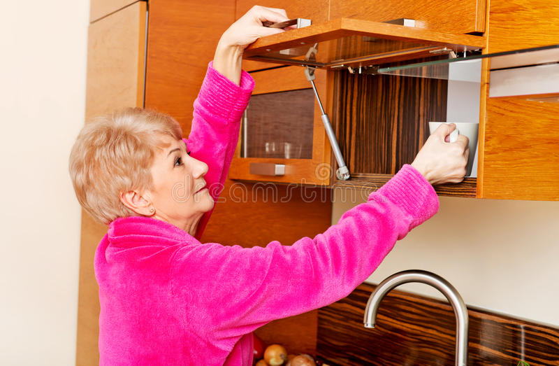 Smile senior woman taking mug from a kitchen cabinet.  royalty free stock photos
