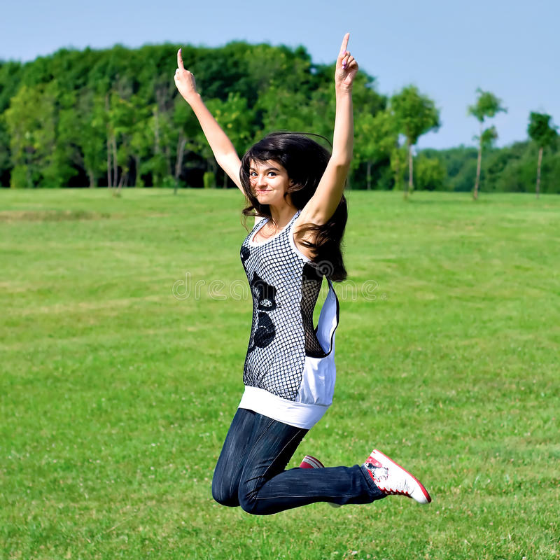Smile teen open hands jumping on the meadow stock images