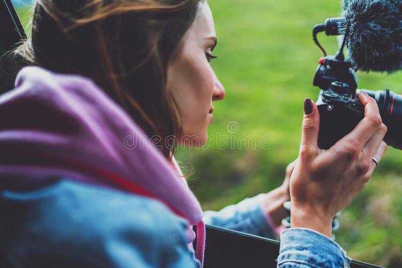 Smile tourist girl in an open window of a auto car taking photography click on digital photo camera, photographer look on camera royalty free stock photography
