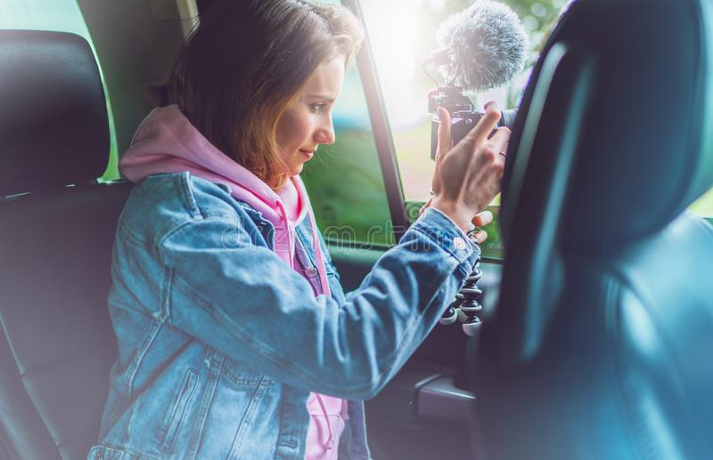 Smile tourist girl in an open window of a auto car taking photography click on digital photo camera, photographer looking on camer royalty free stock photo