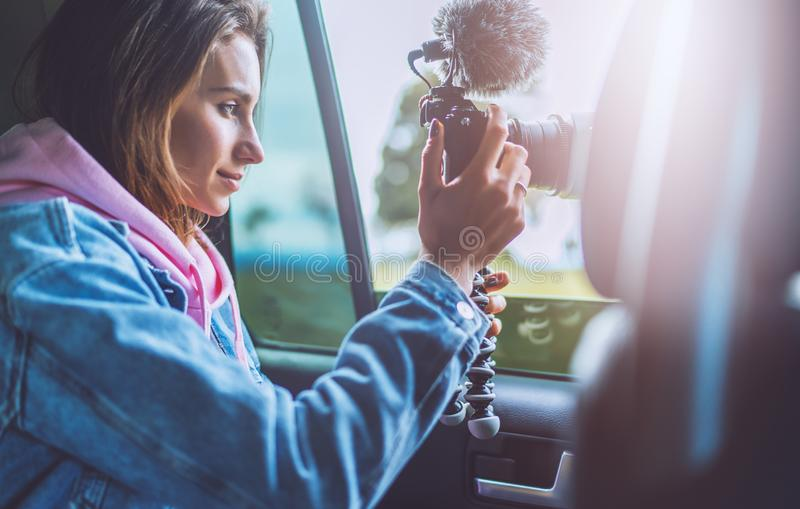 Smile tourist girl in an open window of a auto car taking photography click on digital photo camera, photographer looking on camer stock photo