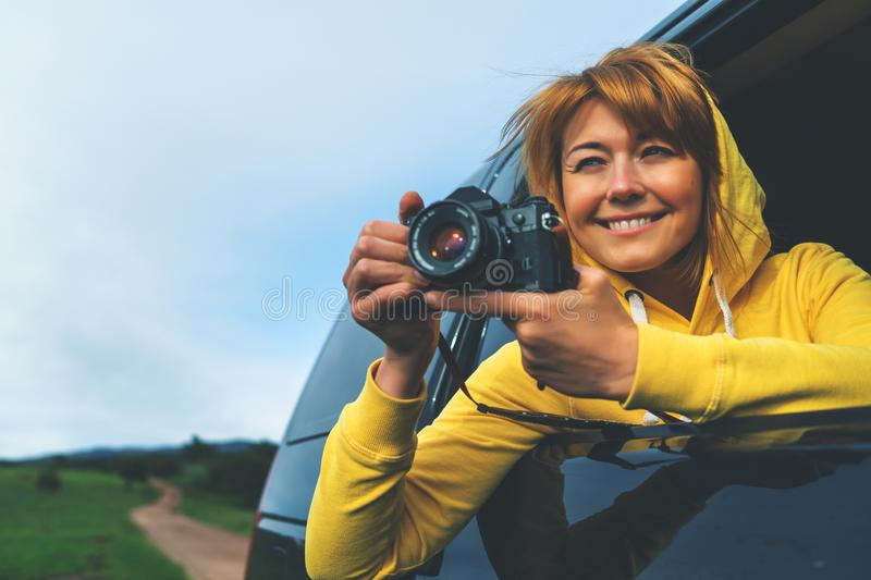Smile tourist girl in an open window of a auto car taking photography click on retro vintage photo camera, photographer looking royalty free stock photography