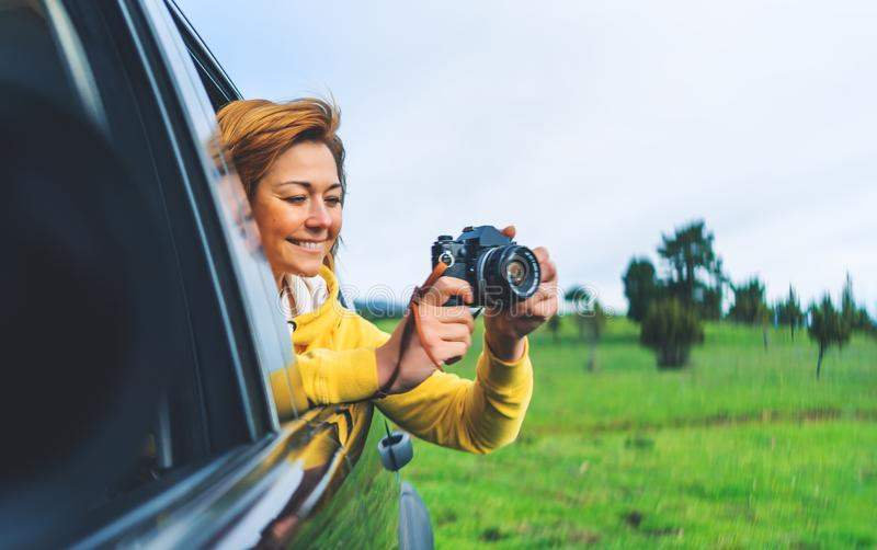 Smile tourist girl in an open window of a auto car taking photography click on retro vintage photo camera, photographer looking royalty free stock photo