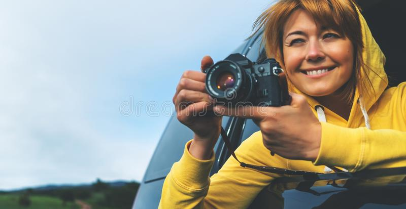 Smile tourist girl in an open window of a auto car taking photography click on retro vintage photo camera, photographer look royalty free stock photos