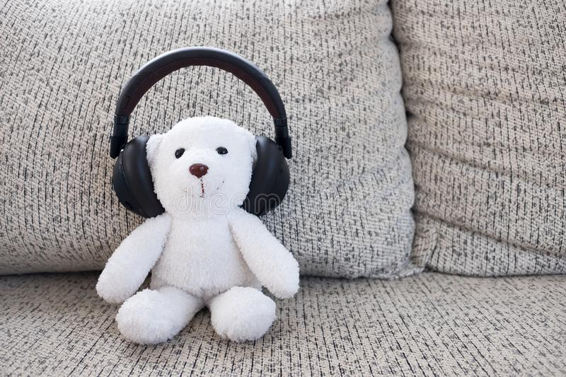 Smile white teddy bear sitting on sofa and wearing headphone royalty free stock image