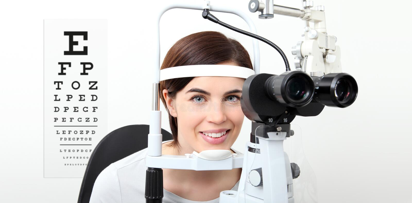 Smile woman doing eyesight measurement with slit lamp and visual. Test chart on white royalty free stock image