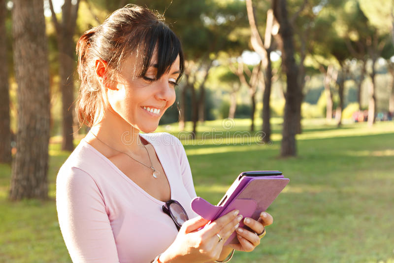Smile Woman reading her ebook. Outdoor royalty free stock photos