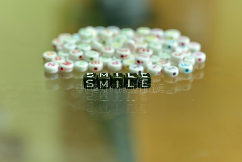 SMILE  written with Acrylic Black cube with white Alphabet Beads on the Glass Background.  royalty free stock photos