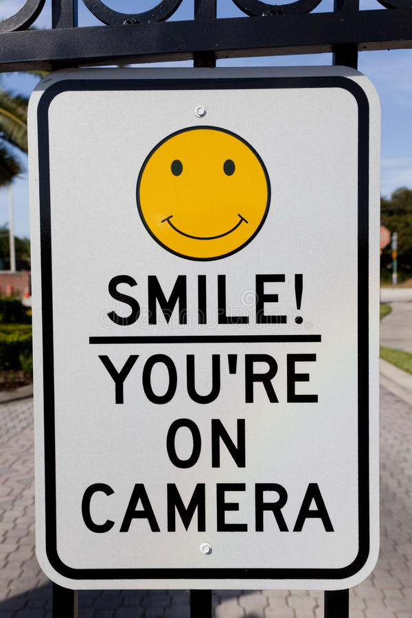 Smile You're On Camera Security Sign. A Smile You're on Camera sign affixed to security gates stock photography