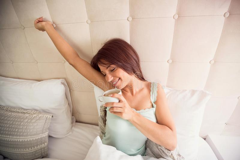 Young brunette enjoys in aromatic morning coffee in bed royalty free stock image