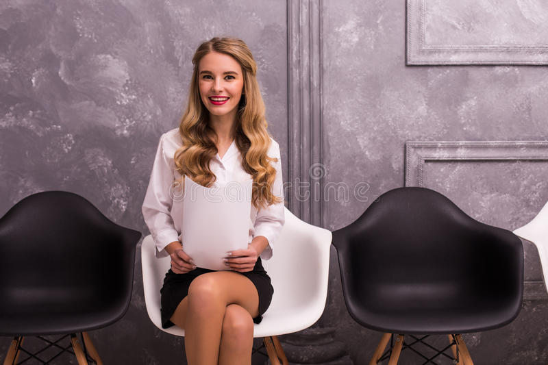 Smile young businesswoman holding paper while sitting on chair. Against grey background royalty free stock photography