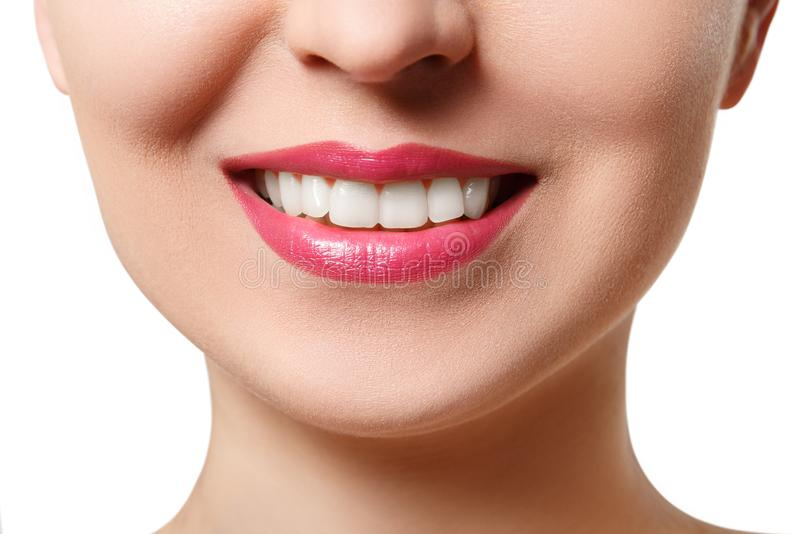 The smile of a young woman with perfect white teeth. close-up isolated on white stock image