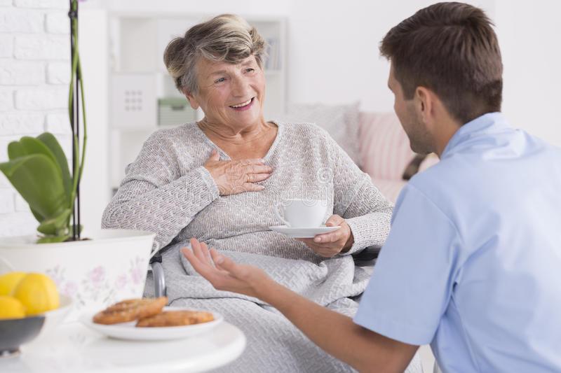 Smiled elder woman and her young male nurse. Talk between the smiled elder women and her young male nurse royalty free stock photos