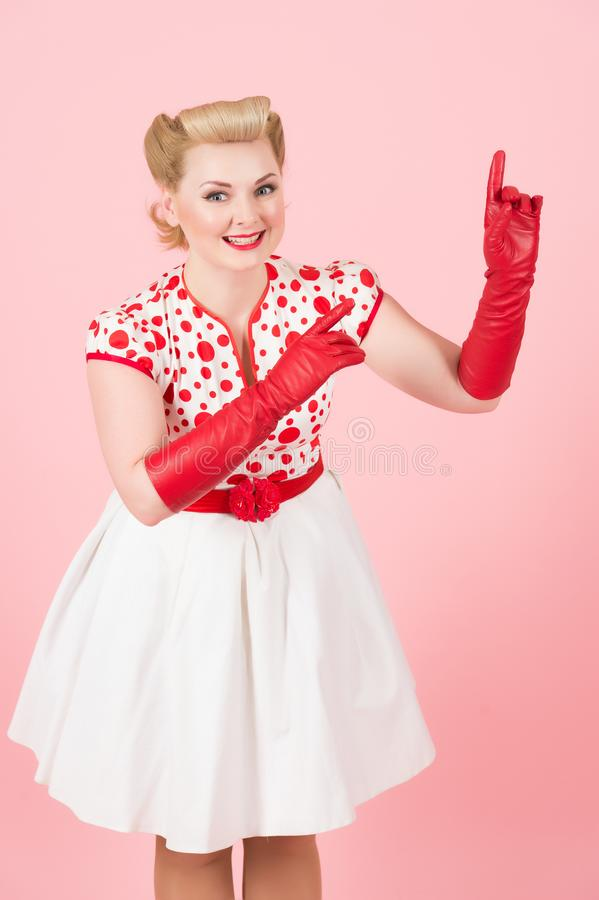 Smiled and happy blonde girl sales space on pink background. Blonde girl pointing by fingers up. Lady with red gloves on hands poi royalty free stock photography