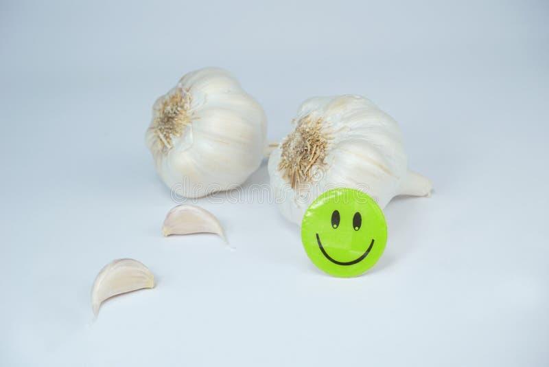 Smiley счастливая сторона на свежем органическом чесноке изолированном на белой предпосылке стоковое фото