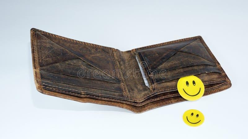 Smiley счастливые стороны падая из открытого кожаного бумажника стоковые изображения