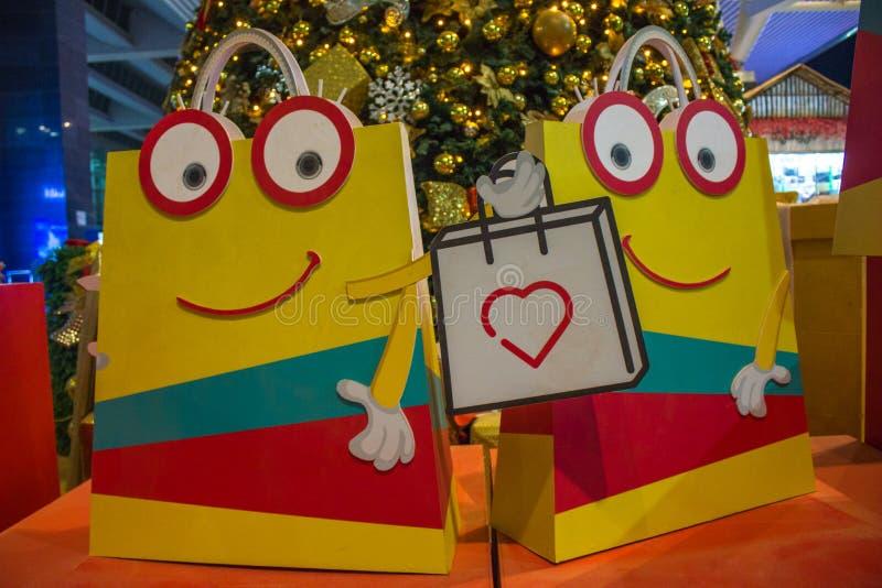 Smiley belebte Einkaufstaschen mit Weihnachtsbaum im Hintergrund stockfotografie