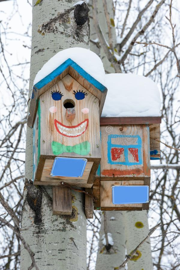 Smiley birdhouses. Birdhouse in the form of a funny face on the tree. Handmade wooden nesting box covered in snow. Winter landscap. E with trees covered of the stock photo