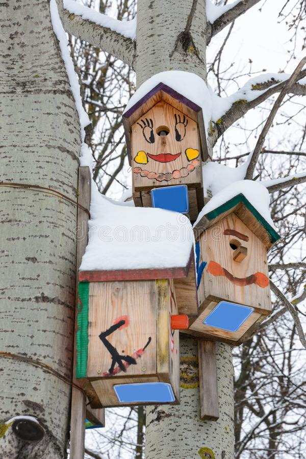 Smiley birdhouses. Birdhouse in the form of a funny face on the tree. Handmade wooden nesting box covered in snow. Winter landscap. E with trees covered of the royalty free stock photo