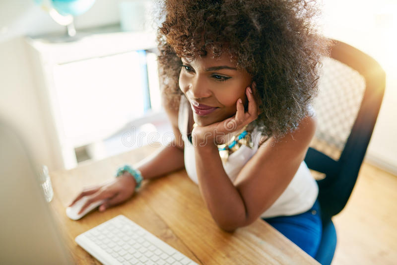 Smiley black woman using small business computer stock photo