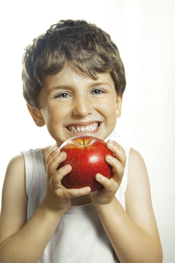 Smiley chłopiec z czerwonym jabłkiem zdjęcia stock