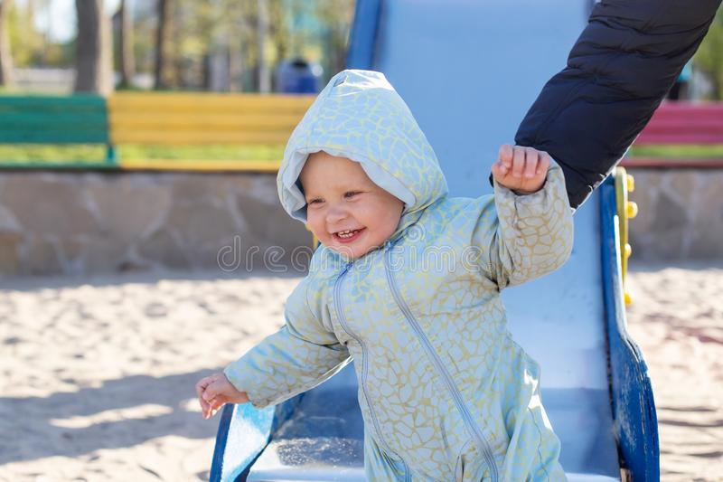 Smiley child in a blue jumpsuit rides a slide. Family outdoor lifestyle royalty free stock photos