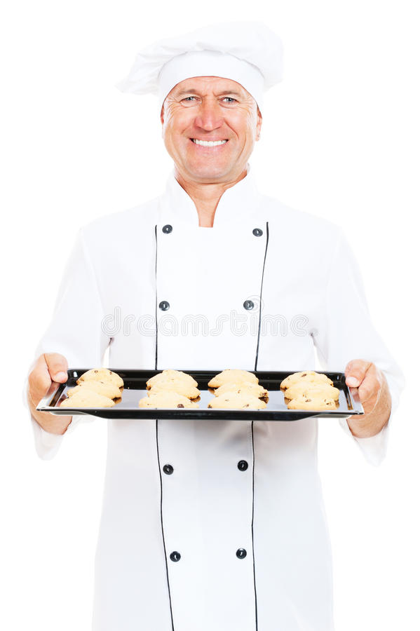 Smiley cook holding baking tray with cookies royalty free stock image