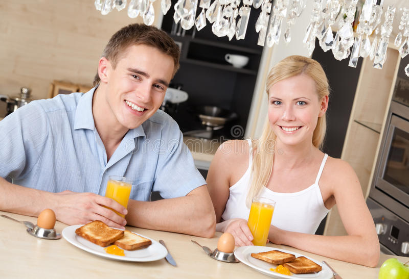 Smiley couple have breakfast in the kitchen stock photography