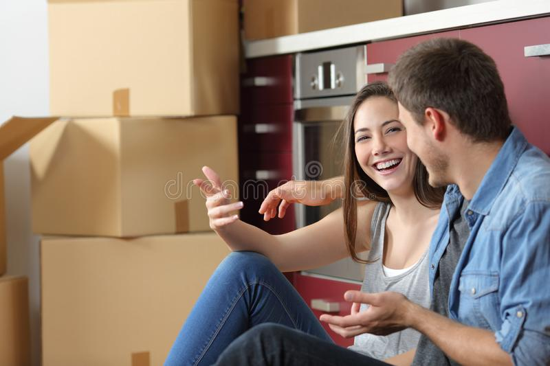Smiley couple moving home talking on the floor royalty free stock images