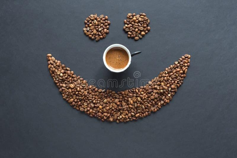 Smiley de los granos de café con la taza de café en el fondo negro imágenes de archivo libres de regalías