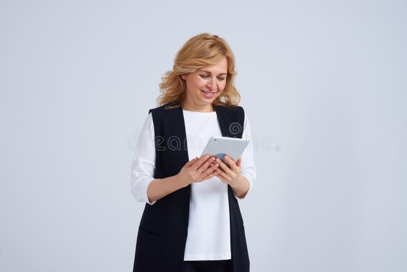 Smiley dojrzała kobieta używa pastylka komputer osobistego obrazy royalty free
