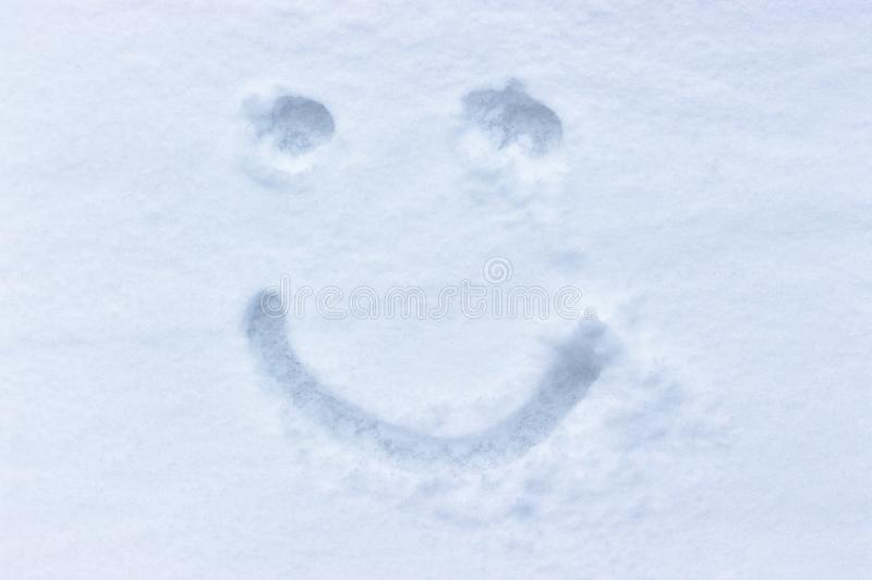 Smiley drawing in the snow. Woman in the fresh, untouched snow. Graza and smile, emoji. Pure White Fresh Fluffy Snow royalty free stock image