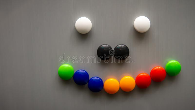 Smiley emoji using the colorful fridge magnet on the refrigerator. Art and creative concept. Kids toy. Selective angle and focus stock image