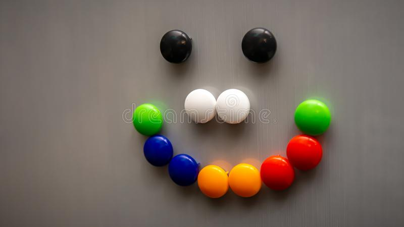 Smiley emoji using the colorful fridge magnet on the refrigerator. Art and creative concept. Kids toy. Selective angle and focus royalty free stock photo