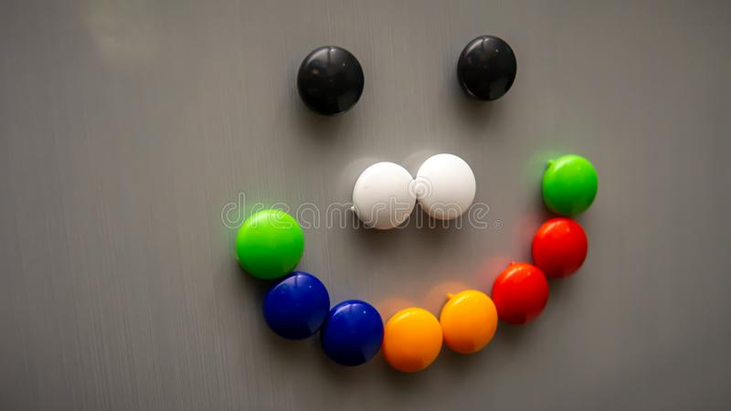 Smiley emoji using the colorful fridge magnet on the refrigerator. Art and creative concept. Kids toy. Selective angle and focus stock photography