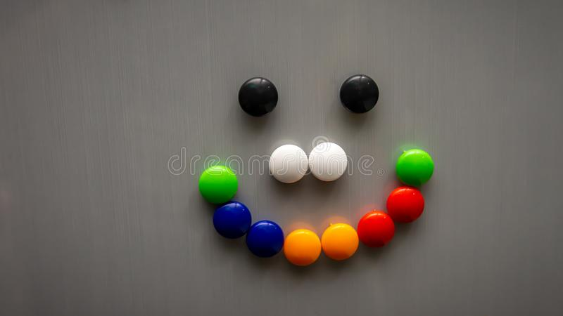 Smiley emoji using the colorful fridge magnet on the refrigerator. Art and creative concept. Kids toy. Selective angle and focus stock images