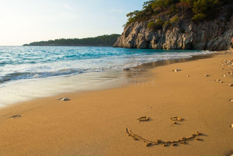 Smiley escrito en la playa arenosa imágenes de archivo libres de regalías